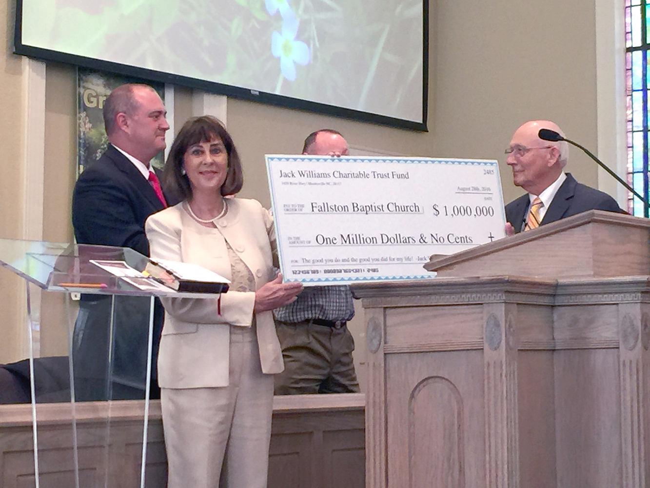Rev. David Blanton (right) of the Fallston Baptist Church gives a look of congratulations to deacons of the Church as a check for $l million was given to the Church for construction of an activities center. The check was given from the trust of Jack R. Williams, owner of Queens Landing in Mooresville. Williams had been a member of the Church for 72-years and passed away on January 5, 2016. Presenting the check of his behalf was Queens Landings Vice-President Deborah Harwell.