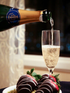 Bottle pouring a glass of champagne with chocolate cover strawberries.